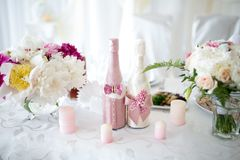 Two wedding bottles. Big Bouquets and Two champagne bottles. Goods for wedding. This photo is perfect for magazines, shops dealing with wedding dresses Royalty Free Stock Photography