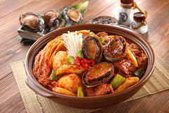 Big bowl of abalone kimchi spicy galbijjim with potatoes, beef,. Onion and mushroom on wooden korean table deliciously Royalty Free Stock Photos