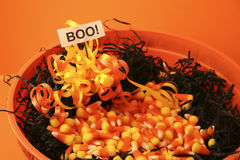 Big bowl of Halloween candy. Bowl filled with Halloween candy corn and black raffia with a boo sign stock image