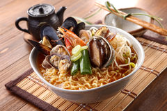 Big bowl of instant noodle with abalone, shrimp, clams, onion an. D sprout on wooden korean table deliciously Royalty Free Stock Images