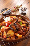 Big bowl of kimchi lunch with abalone, mushrooom, potatoes, beef. And noodle on wooden korean table deliciously Stock Images