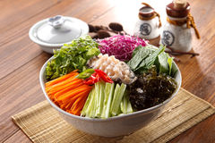 Big bowl of overture hoedeopbap with squid, seaweed, cucumber, o. Nion and ablone on wooden korean table deliciously royalty free stock images