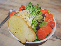 Big bowl of smoked salmon salad with big piece of garlic bread on top. The bowl is placed on wood table with a pair of fork and spoon beside Royalty Free Stock Photos