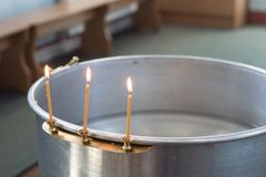 Big bowl of water for the baptism of a baby with wax candles. Orthodoxy. Greek Catholics royalty free stock image