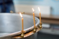 Big bowl of water for the baptism of a baby with wax candles. Orthodoxy. Greek Catholics. macro stock photography
