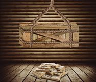 Big box suspended above money. Big wooden box suspended above a pile of money in the room Stock Image