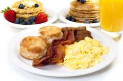 Big Breakfast. Breakfast plate with scrambled eggs, bacon, and buttermilk biscuits.  Waffles, pancakes, and orange juice in background.  Isolated on white Stock Photos
