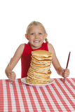 Big Breakfast. Little girl with a giant plate of pancakes, a knife and fork on a table cloth. Shallow DOF with focus on the pancakes stock photos
