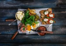 Big breakfast. Sausages, brusquets, fried eggs, potato cheese and greens with sauce. Top view. Stock Images