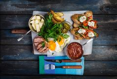 Big breakfast. Sausages, brusquets, fried eggs, potato cheese and greens with sauce. Top view. Royalty Free Stock Photos