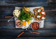 Big breakfast. Sausages, brusquets, fried eggs, potato cheese and greens with sauce. Top view. Royalty Free Stock Image