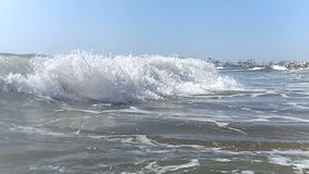 Big breeze waves close-up in slow motion, moving towards the shore. The spray from the wave glistens in the sun, and stock video
