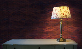 Big brick wall and light lamp on white table. Use for multipurpose Stock Images