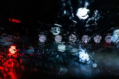 Blurred car lights on wet windows stock photography