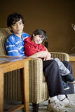 Big brother caring for disabled sibling. Big brother taking care of disabled sibling with cerebral palsy Stock Image