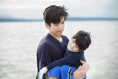 Big brother carrying disabled boy by lake shore Royalty Free Stock Photos