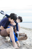 Big brother holding disabled boy on beach Stock Photos