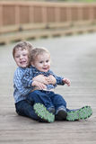 Big brother holding little brother in lap Stock Images