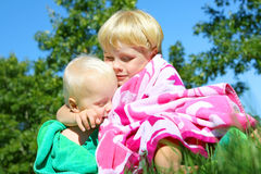 Big Brother Hugging Baby Outside in Beach Towels Stock Images