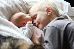Big Brother Hugging Newborn Baby with Love. A 5 year old big brother is hugging, smiling, and looking at his newborn baby sister as they sunggle in bed Royalty Free Stock Photo