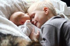 Big Brother Hugging Newborn Baby med förälskelse Royaltyfri Foto