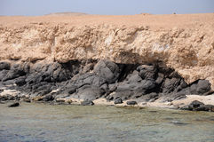 Big Brother Island in the Red Sea. The volcanic rocks of the island base Stock Photography