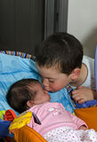 Big brother kisses baby sister Stock Photos
