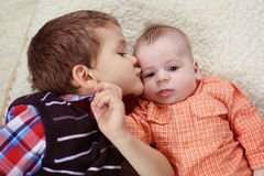 Big brother kissing the baby Stock Photos
