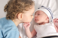 Big brother kissing his little sibling. Stock Images