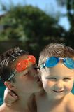 Big brother and little brother. Big brother smooching his baby brother on the cheek while swimming Stock Photography