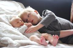 Big Brother Lovingly Playing con la hermana recién nacida del bebé Fotografía de archivo