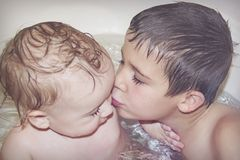 Big brother plays with little brother in the bathroom and kisses him on the cheek Royalty Free Stock Image