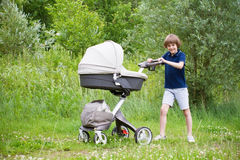 Big brother pushing a stroller in the park Royalty Free Stock Images