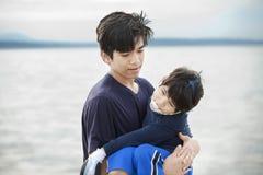 Big brother que carreg o menino incapacitado pela costa do lago Fotos de Stock Royalty Free