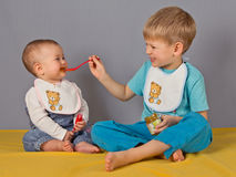 Big brother spoon-feeds  his little sister. Royalty Free Stock Photo