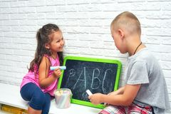 Big Brother Teaches Sister to Write Letters in Summer Holidays. The child learns the letters. Older brother teaches sister alphabet. Outside school education royalty free stock photos