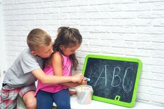 Big Brother Teaches Sister to Write Letters in Summer Holidays. The child learns the letters. Older brother teaches sister alphabet. Outside school education stock photo