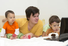 Big brother watching cartoons with his younger sisters at laptop Stock Photo