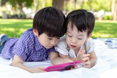 Big brother and younger brother are watching cartoons on tablet at park. Cute young boys are brotherhood. Lovely children always stock photo