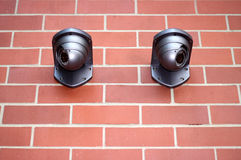 Big Brothers. Two surveillance cameras keep watch against an authoritative brick background stock image