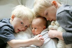 Big Brothers Hugging Newborn Baby Sister Stock Images