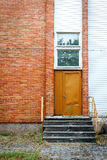 Big brown door on a red brick and white planks wall Stock Photos