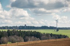 Big brown fields of fertile soil, green forest and wind power in. The background royalty free stock photos