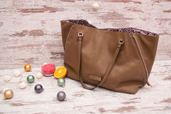 Big brown ladies handbag on a wooden background, Christmas ornaments, garland and candle. fashion concept Stock Images