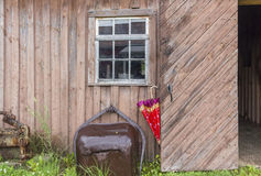 Big brown mud bucket leaning against an old barn exterior wall. Royalty Free Stock Photography