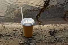 Paper glass with coffee on a wet ground near the water royalty free stock photo