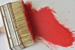 Big brush with red oil paint. Image of a brush on a background of red oil paint Stock Image