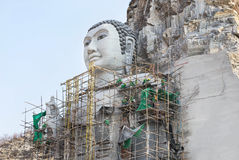 Big buddha carved from stone on the mountain under construction in public thai temple. At suphanburi thailand Stock Photos