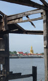 Big Buddha sculpture view through Wooden house ruin on river bank Stock Image