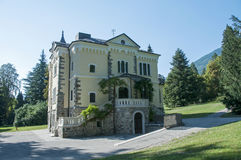 Big building in Italy in the place Levico Terme. With green trees and grass around stock image